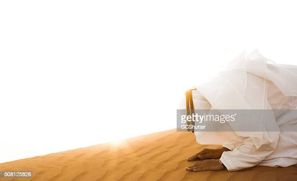 middle eastern arab man praying in desert - allah stock pictures, royalty-free photos & images