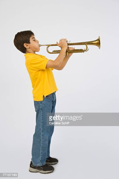 Middle Eastern boy playing trumpet
