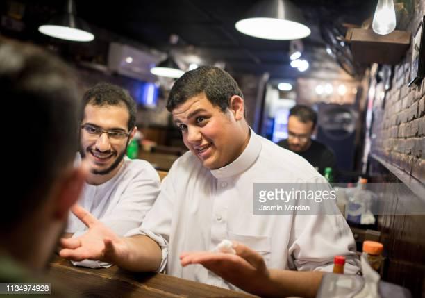 middle eastern boys having conversation at restaurant - chubby arab photos et images de collection