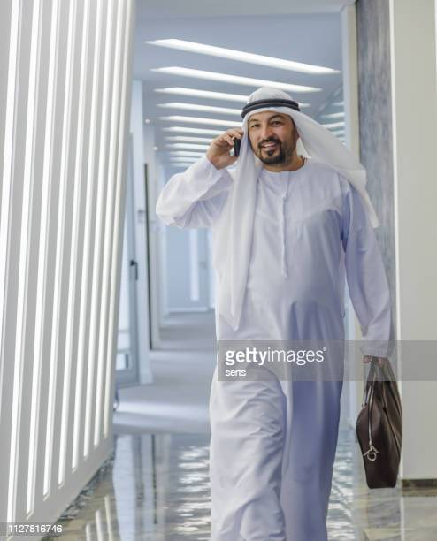 Middle Eastern Businesman with bag walking to modern office corridor