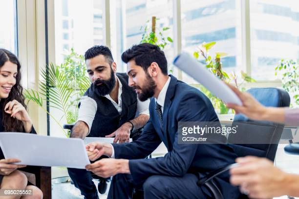 middle eastern business executives huddling over a brainstorming session - bahrain stock pictures, royalty-free photos & images