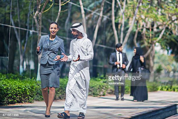 Middle Eastern business people talking in the street