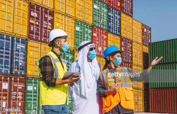 middle eastern businessman and engineers with face mask working outside on a large commercial dock during pandemic - gulf countries stock pictures, royalty-free photos & images