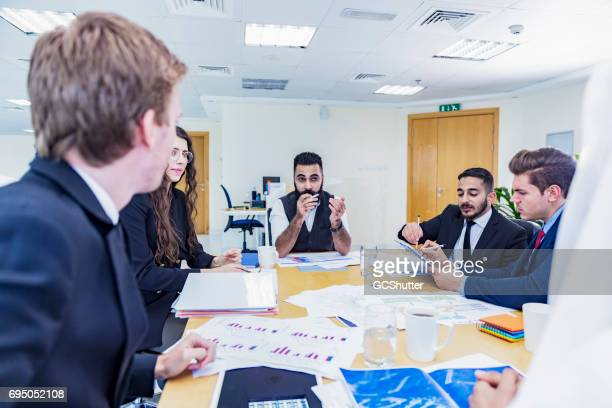 middle eastern businessman chairing a strategy meeting - chairperson stock pictures, royalty-free photos & images