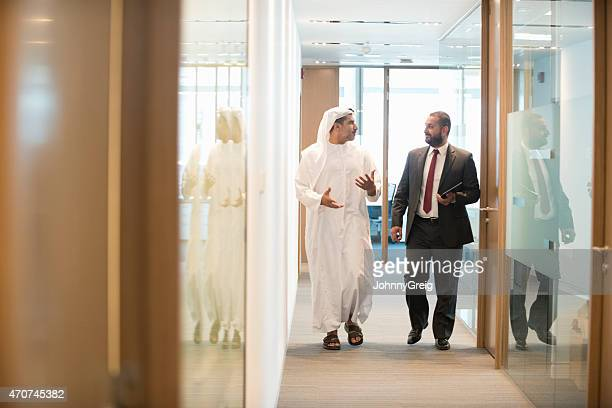 Middle Eastern businessman discussing office in office corridor