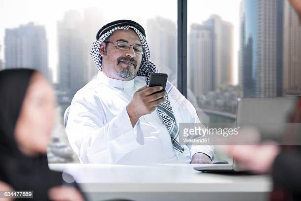 Middle Eastern businessman in office using smart phone