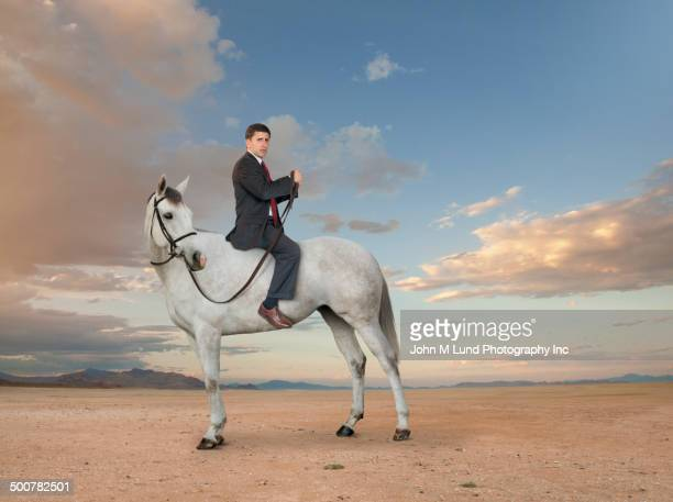 Middle Eastern businessman riding horse backwards