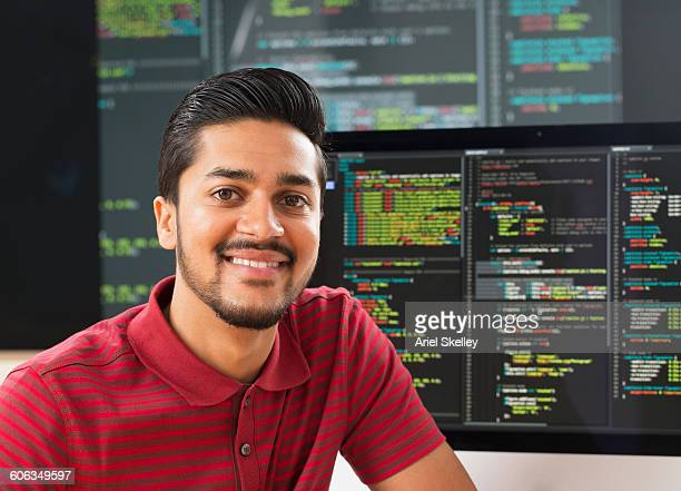 Middle Eastern businessman smiling at computer