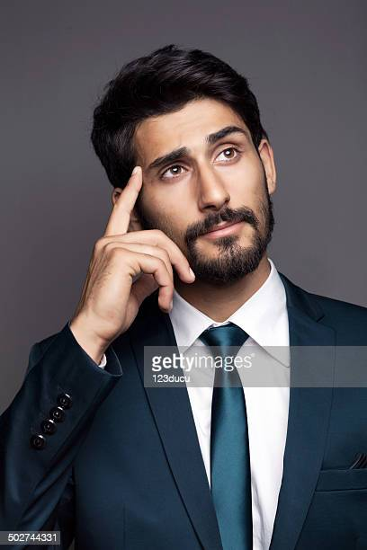 middle eastern businessman thinking - handsome pakistani men stock photos and pictures