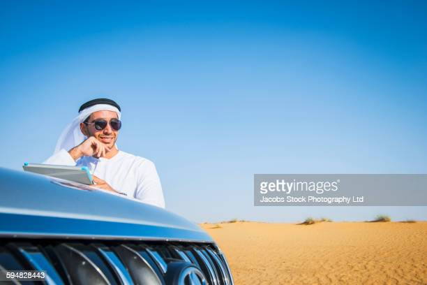Middle Eastern businessman using digital tablet in desert