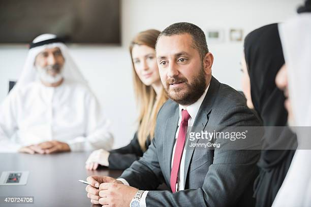 middle eastern businessman with colleagues at conference table - middle eastern culture stock pictures, royalty-free photos & images