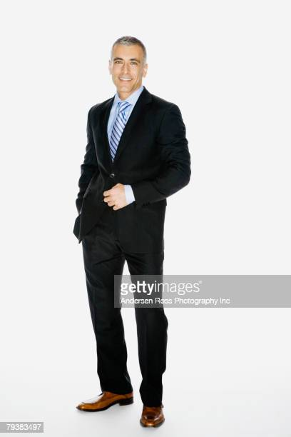 middle eastern businessman with hand on jacket button - freisteller neutraler hintergrund stock-fotos und bilder