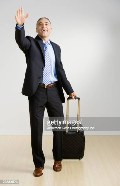 middle eastern businessman with suitcase waving - waving gesture stock photos and pictures