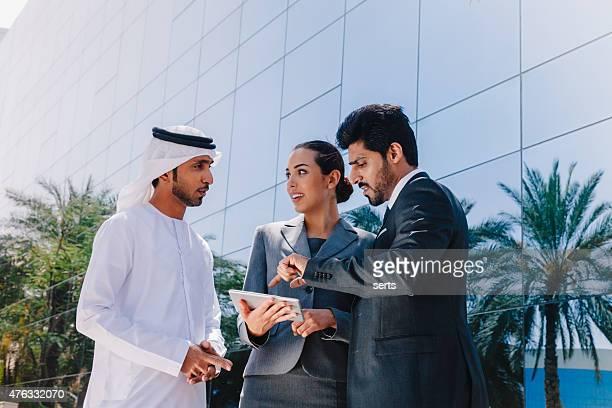 Oriente Medio empresarios y empresaria de trabajo con tableta Digital al aire libre