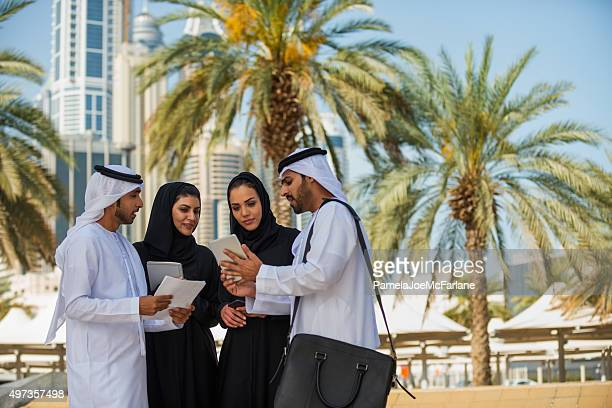Middle Eastern Businessmen and Businesswomen Reviewing Computer Tablet, Dubai, UAE