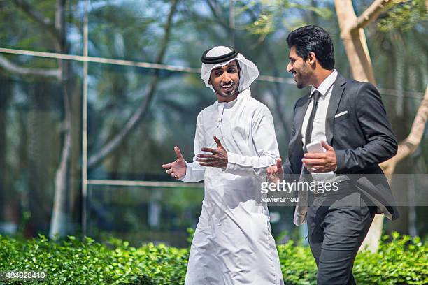 middle eastern businessmen talking in the street - united arab emirates stock pictures, royalty-free photos & images