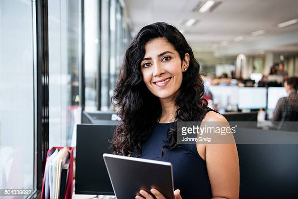 middle eastern businesswoman with tablet smiling towards camera - 35 39 years stock pictures, royalty-free photos & images