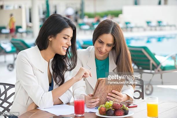 Middle Eastern Geschäftsfrauen ReviewingTablet PC am Café im Freien