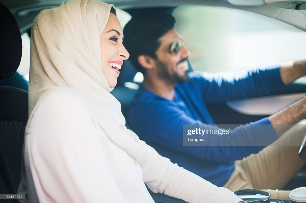 Middle eastern couple driving a luxury car in Dubai : Stock Photo