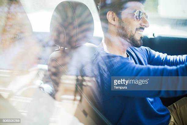 Middle eastern couple driving a luxury car in Dubai