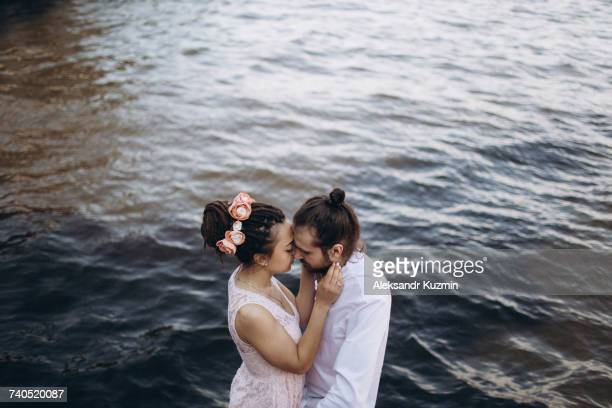 Middle Eastern couple embracing near water