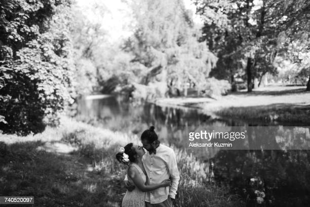 Middle Eastern couple hugging in park near river