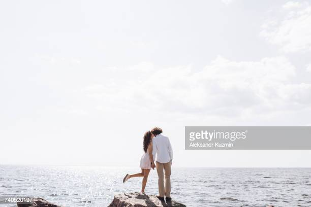 Middle Eastern couple kissing on rocks near ocean