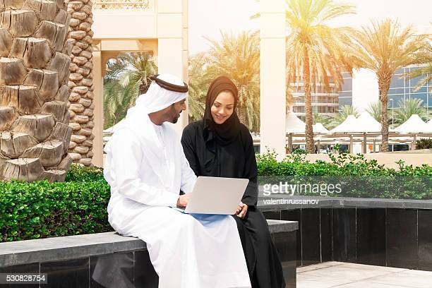 Middle Eastern couple using laptop in the park