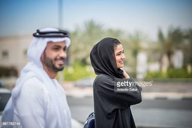 Middle eastern couple wearing traditional clothing walking along street, Dubai, United Arab Emirates