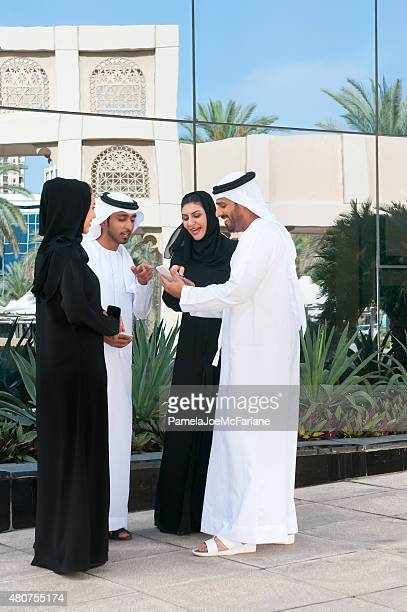 Middle Eastern Couples in Park Laughing and Looking at Cellphones