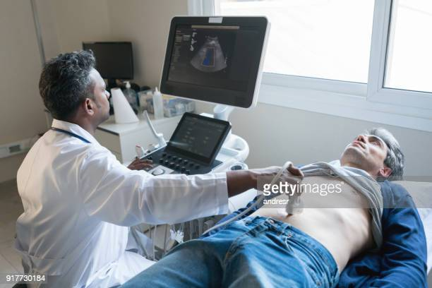 Middle eastern doctor doing an ultrasound scan to a middle aged man