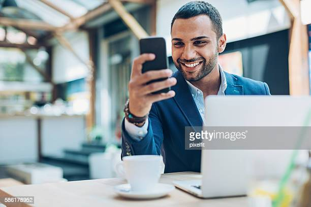 middle eastern ethnicity businessman texting in cafe - naher und mittlerer osten stock-fotos und bilder