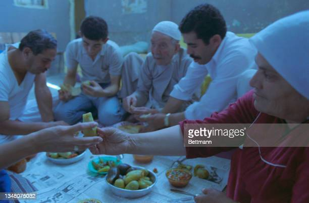 Middle Eastern family enjoying a meal, bowls of food arranged on the floor before them, at home in an unspecified area of the West Bank, 1988.