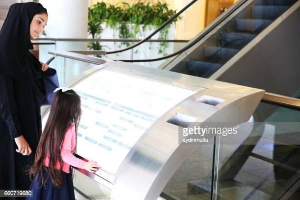 middle eastern family in shopping mall - touch sensitive stock pictures, royalty-free photos & images