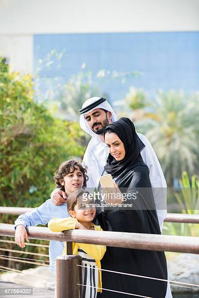 Middle Eastern Family Looking at Selfie on Cellphone in Park