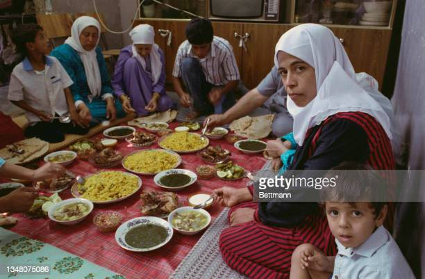 Middle Eastern family sitting around a blanket on which bowls of food are arranged, at a property in an unspecified area of the West Bank, 1988.