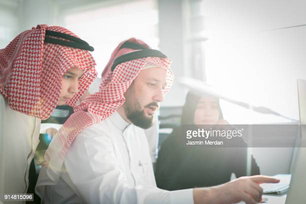 Middle Eastern family together on computer