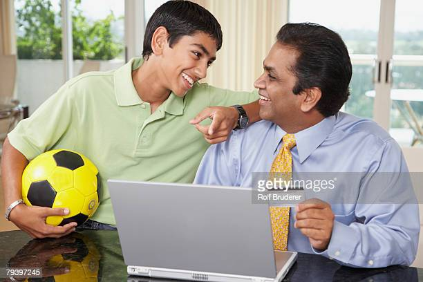 middle eastern father and son shopping online - charging sports stock pictures, royalty-free photos & images