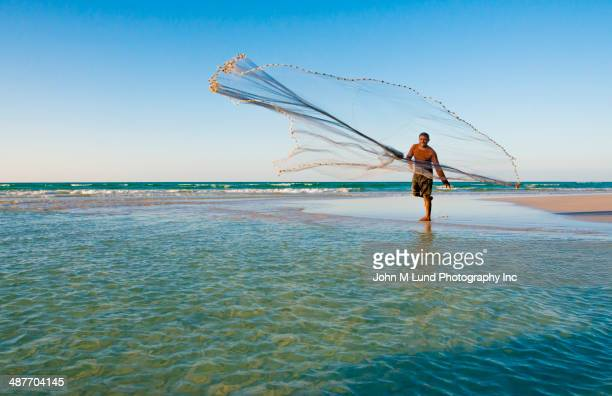 Middle Eastern fisherman casting net on tropical beach