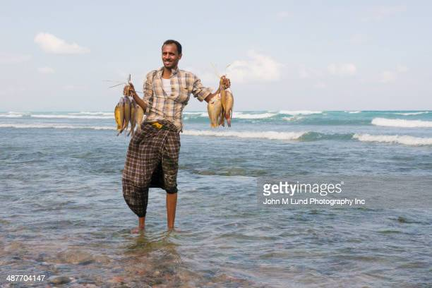 Middle Eastern fisherman holding catch on beach
