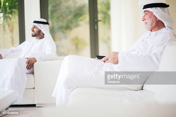 Middle eastern grandfather watching tv at home with son.
