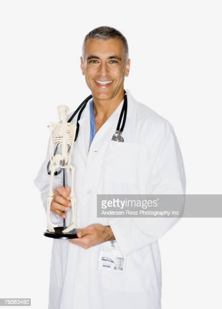 Middle Eastern male doctor holding skeleton model