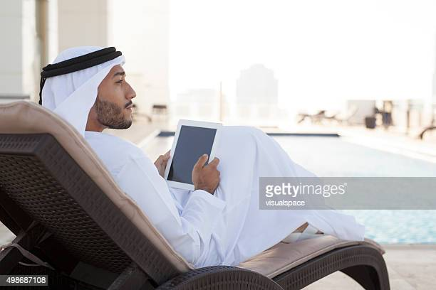 Middle Eastern Man Contemplating by the Pool with iPad