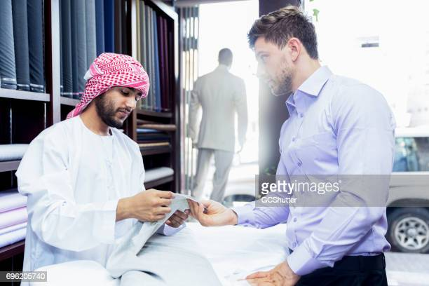 Middle eastern man demonstrating the quality of his product to a customer