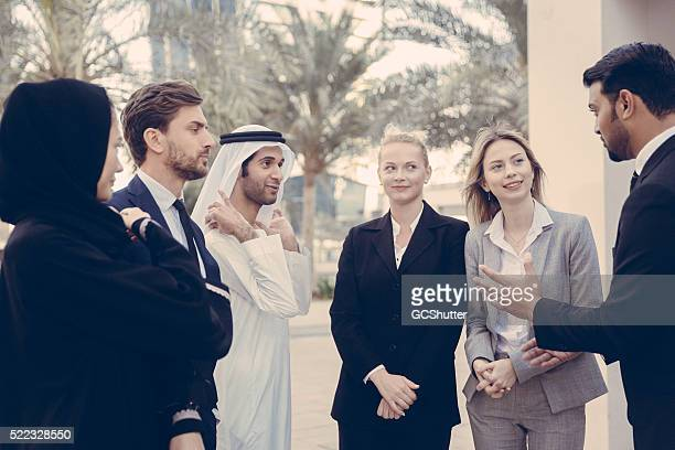 Middle Eastern Man in Suit Leading The Conversation Outdoors
