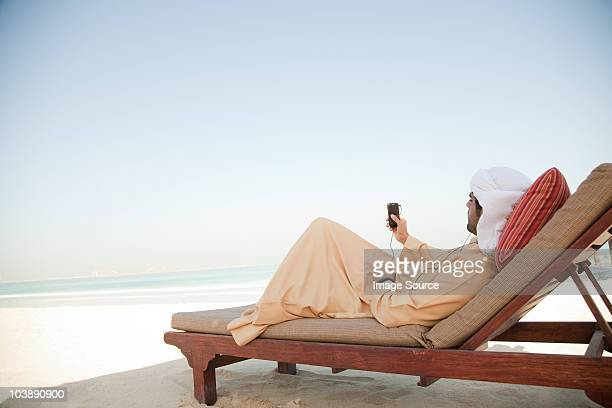 Middle Eastern man listening to music on mobile phone
