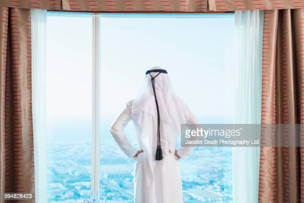 Middle Eastern man looking out hotel window