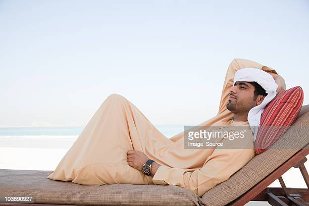Middle Eastern man relaxing on sun lounger