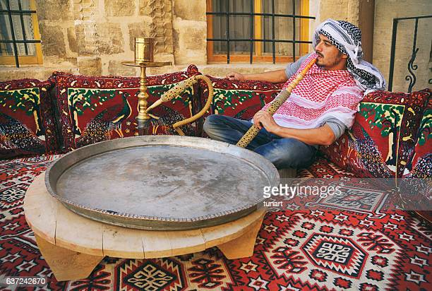 middle eastern man smoking hookah on a traditional couch - hookah stock photos and pictures