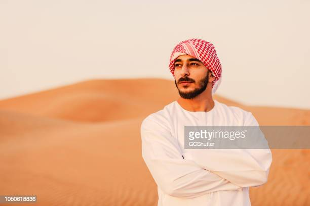 middle eastern man standing armscrossed while admiring the sand dunes - saudi stock pictures, royalty-free photos & images